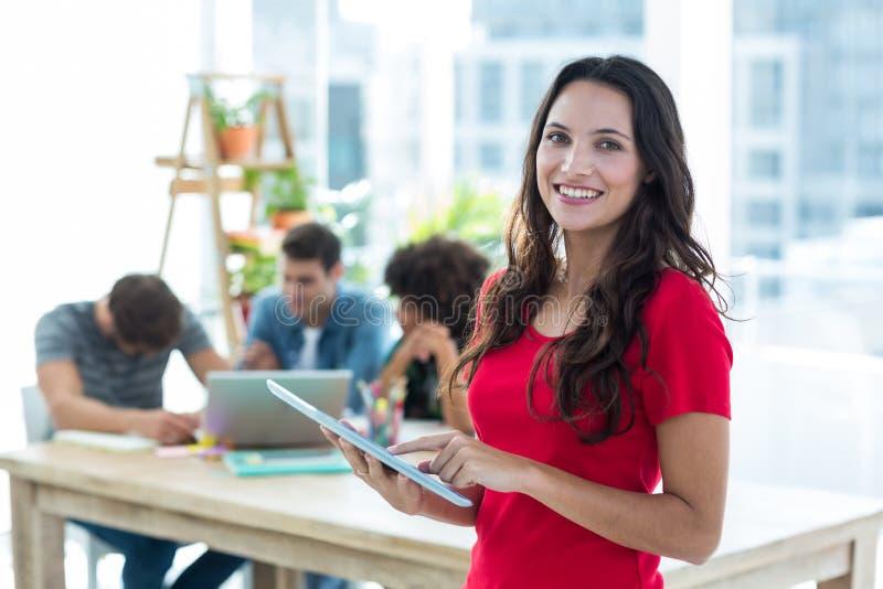 使用片剂的微笑的年轻女实业家 免版税库存照片