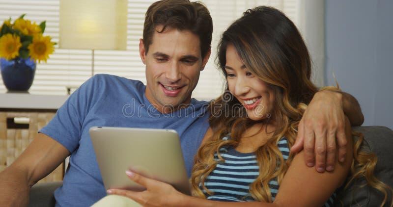 使用片剂的愉快的人种间夫妇一起在长沙发 免版税库存照片