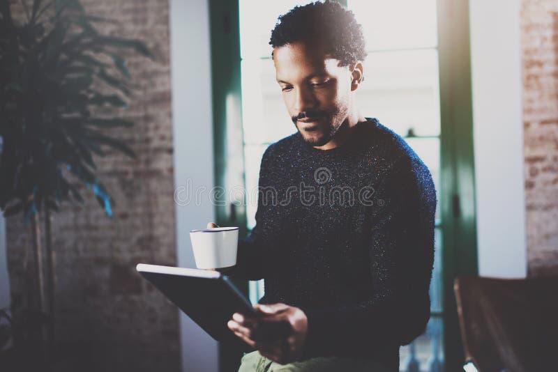 使用片剂的沉思有胡子的非洲人,当拿着白色陶瓷杯子手中在现代coworking的办公室时 概念 库存照片