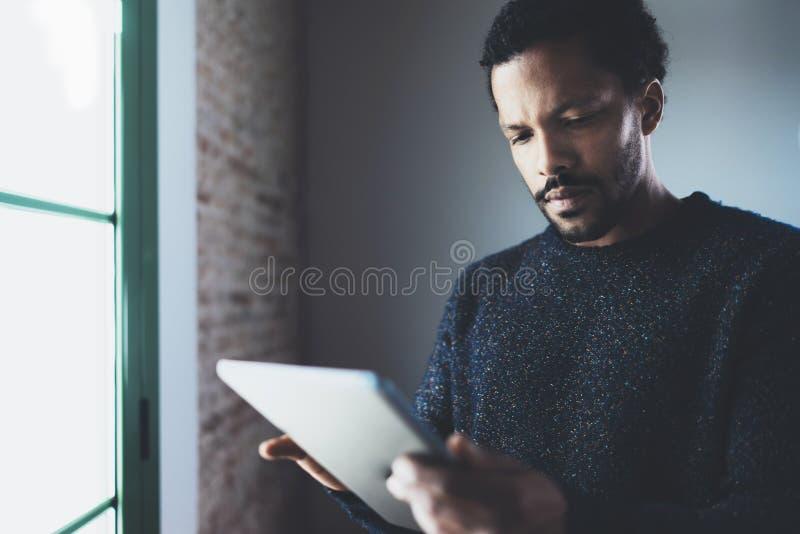 使用片剂的特写镜头观点的沉思有胡子的非洲人,当站立在窗口附近在他的现代公寓时 概念 免版税库存照片