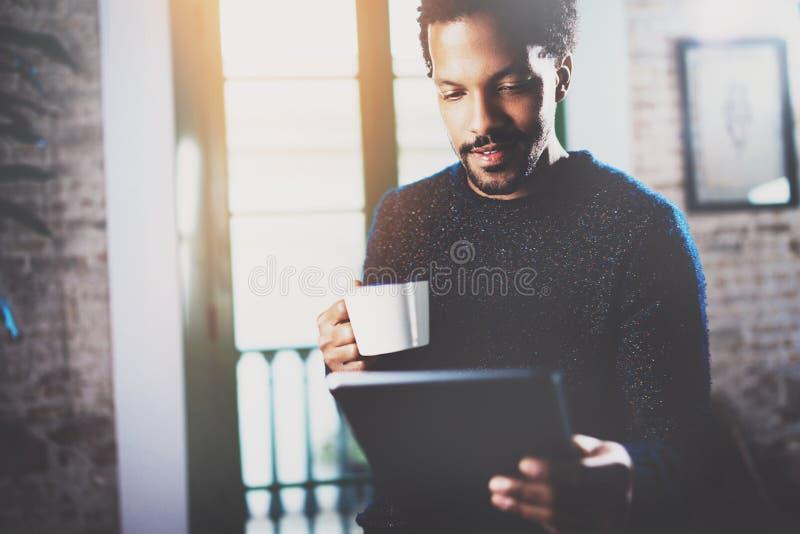 使用片剂的特写镜头观点的年轻有胡子的非洲人,当拿着白色杯子咖啡手中在客厅时 概念 免版税库存图片