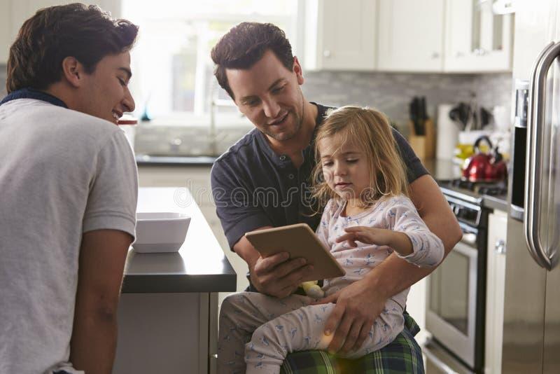 使用片剂的男性快乐夫妇有他们的女儿的在厨房里 库存图片
