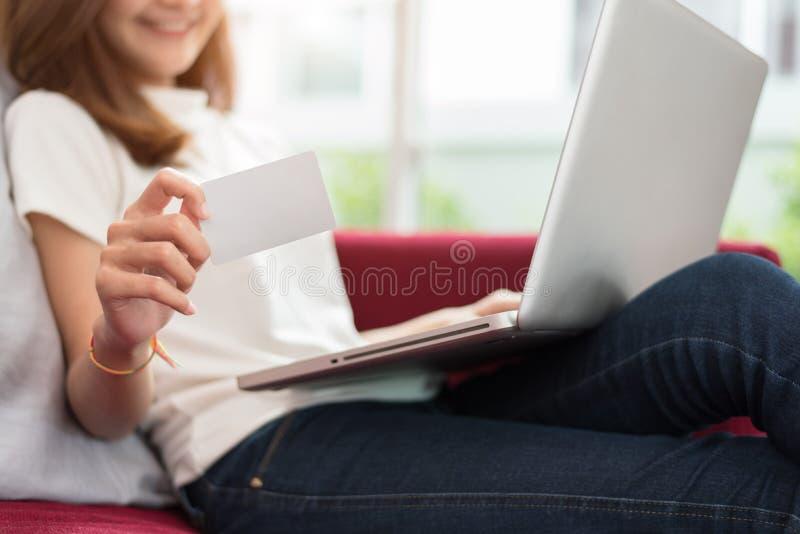 使用片剂的秀丽亚裔妇女和显示信用卡的空白的嘲笑为与高速互联网的网络购物付款 免版税库存图片