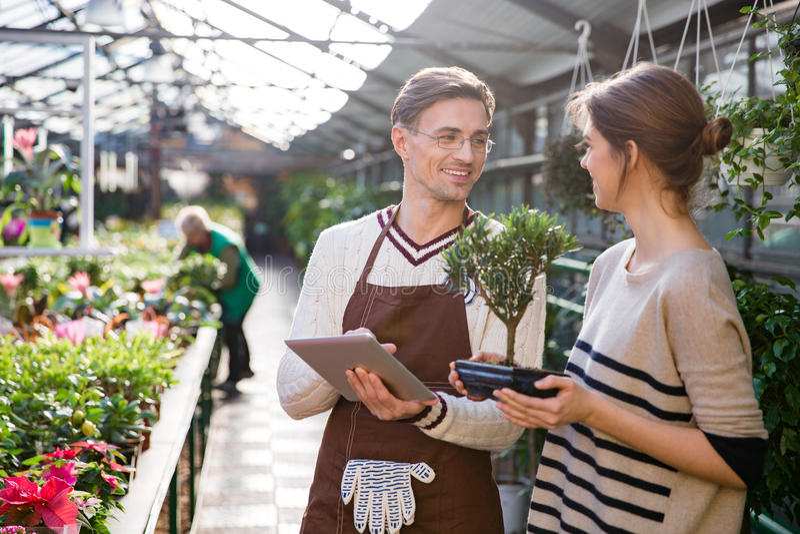 使用片剂的花匠和谈话与拿着盆景树的妇女 免版税库存图片