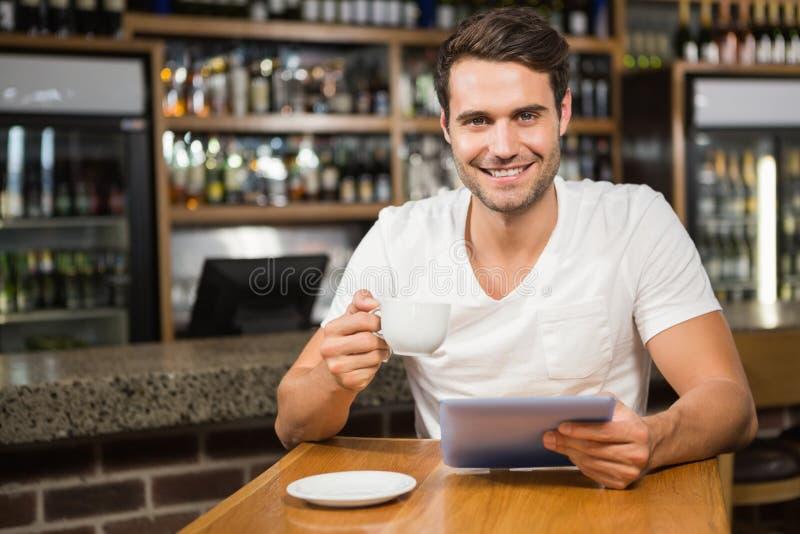 使用片剂的英俊的人和食用咖啡 免版税库存图片
