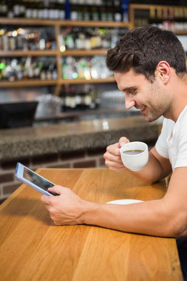 使用片剂的英俊的人和食用咖啡 库存图片