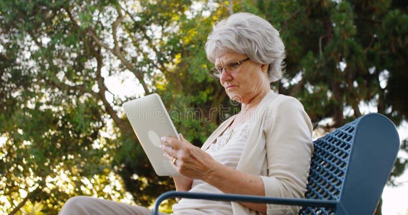 使用片剂的资深妇女在公园 免版税库存图片