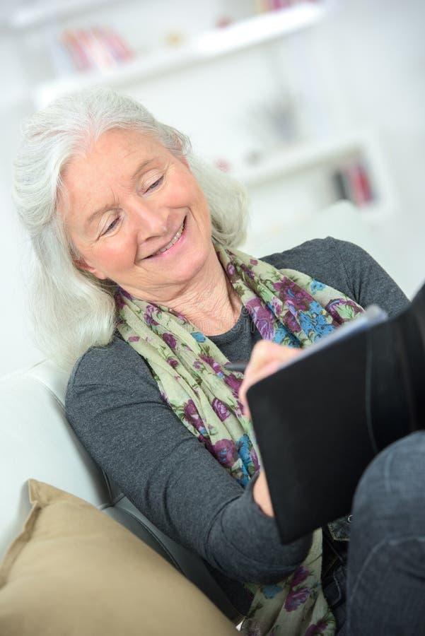 使用片剂的资深妇女在养老院 免版税库存图片