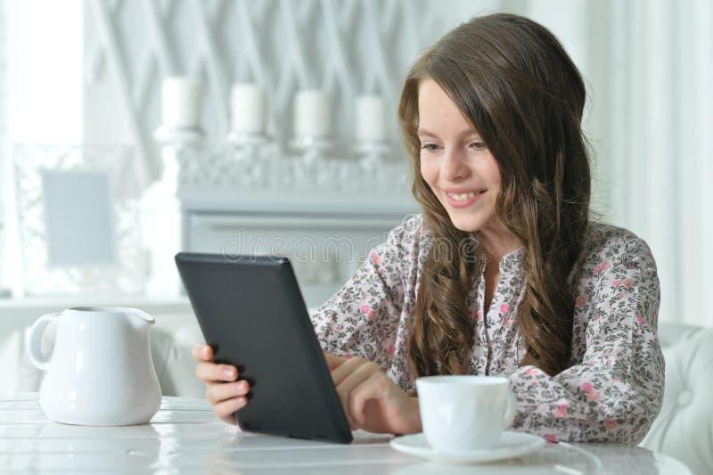 使用片剂的逗人喜爱的女孩特写镜头画象,当喝茶在轻的厨房时 免版税库存照片