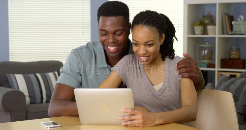使用片剂的年轻黑夫妇在书桌 免版税库存图片