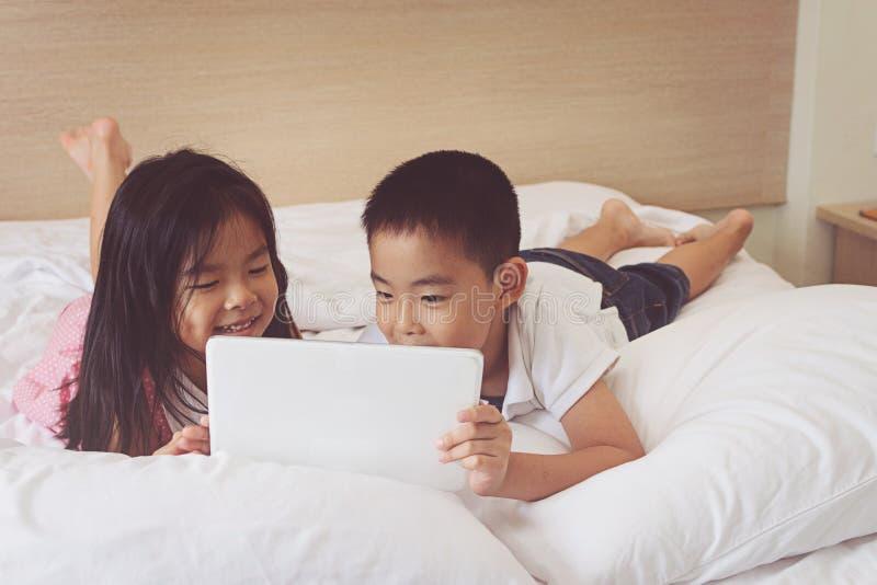 使用片剂计算机的亚裔小男孩和女孩在床 库存照片