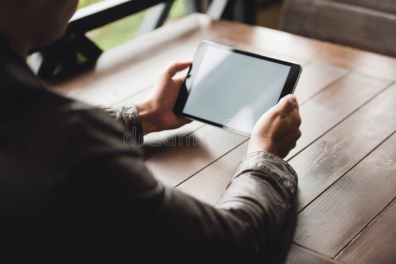 年轻使用片剂计算机的人或学生在咖啡馆 免版税库存图片