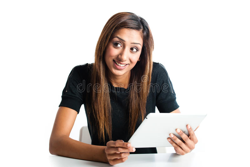 使用片剂计算机的可爱的亚裔印地安少年妇女 库存照片