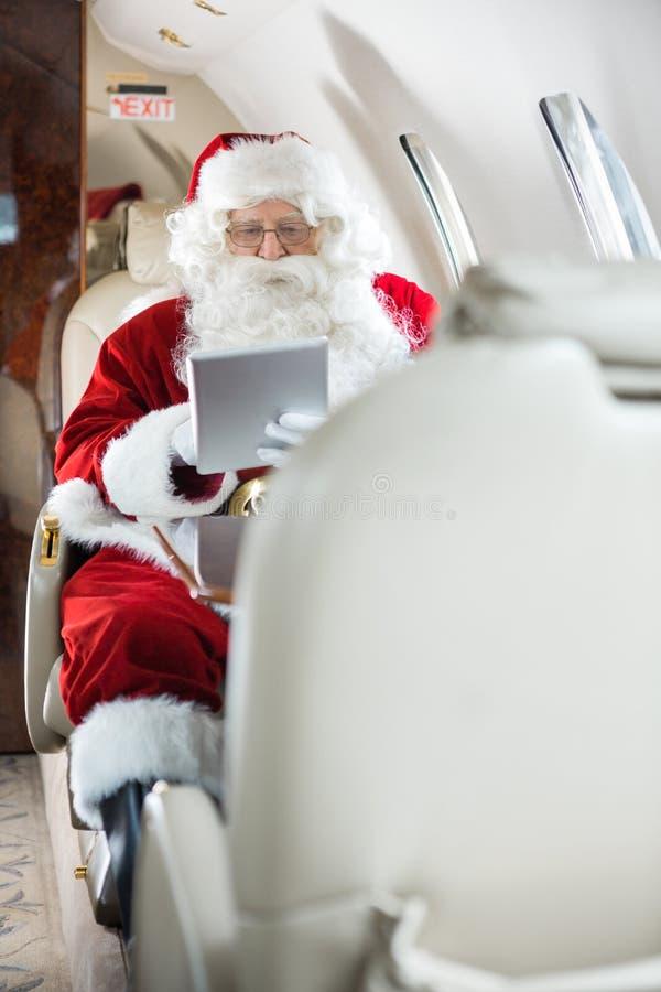 使用片剂计算机的圣诞老人在私人喷气式飞机 免版税库存照片