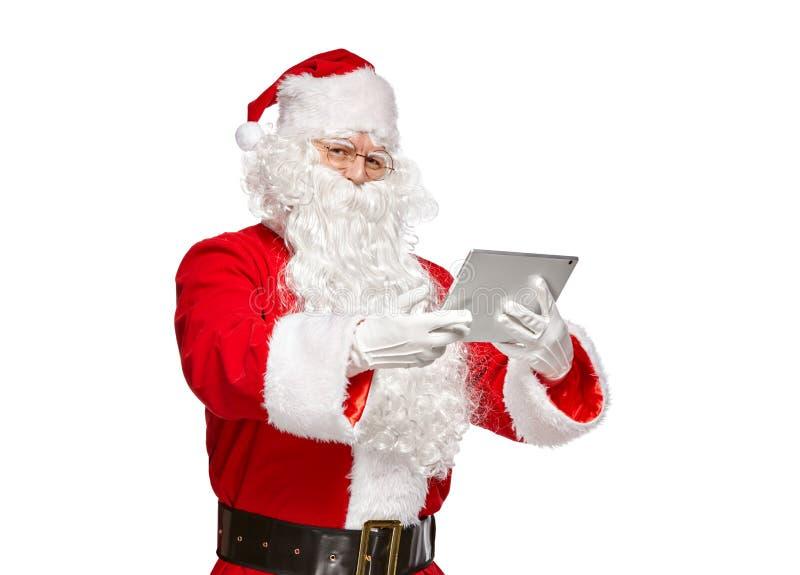 使用片剂计算机的圣诞老人 库存图片