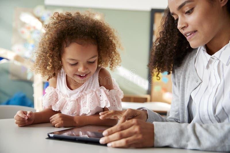 使用片剂计算机的女性婴儿学校老师运转一在一个在有一位年轻混合的族种女小学生的一间教室,selecti 免版税库存照片
