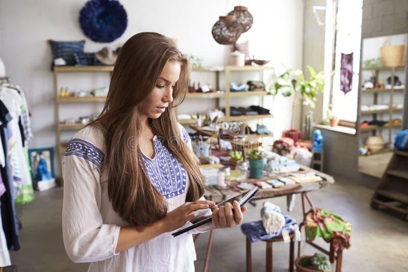 使用片剂计算机的女性精品店经理在商店 免版税库存照片