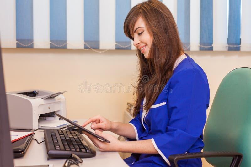 使用片剂计算机的女性医生在医院 她是穿戴 免版税库存照片