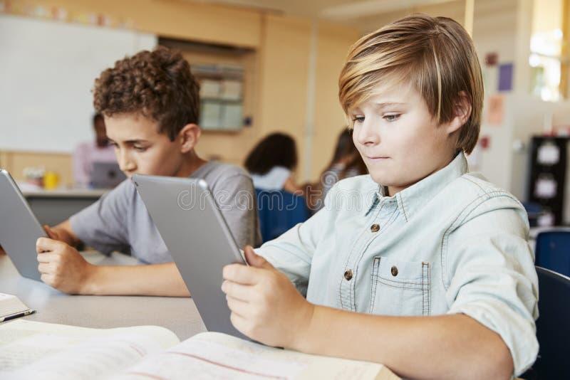 使用片剂计算机的小学男孩在类 图库摄影