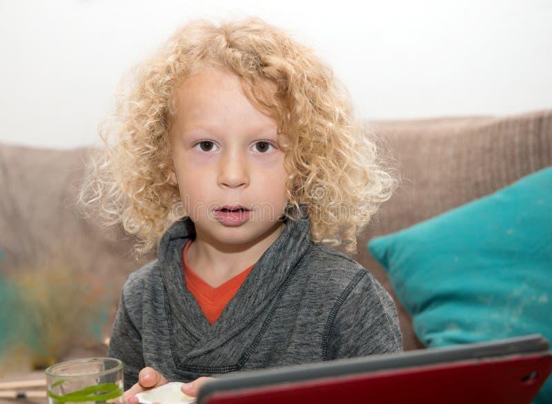 使用片剂计算机的小白肤金发的男孩 库存照片