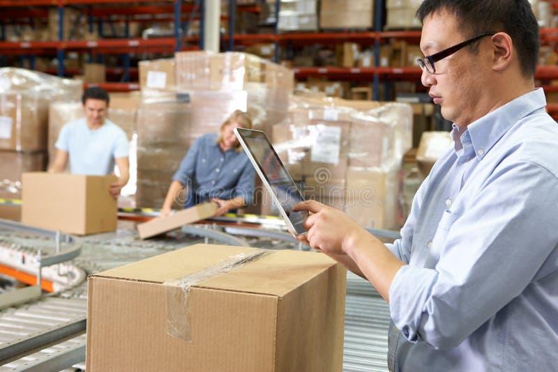 使用片剂计算机的工作者在配给物仓库 免版税库存照片