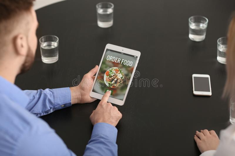 使用片剂计算机的年轻人为预定的食物在办公室 图库摄影