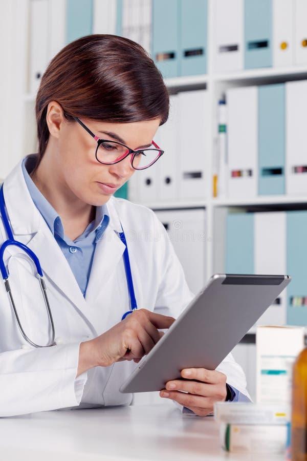 使用片剂计算机的年轻女性医生 库存图片