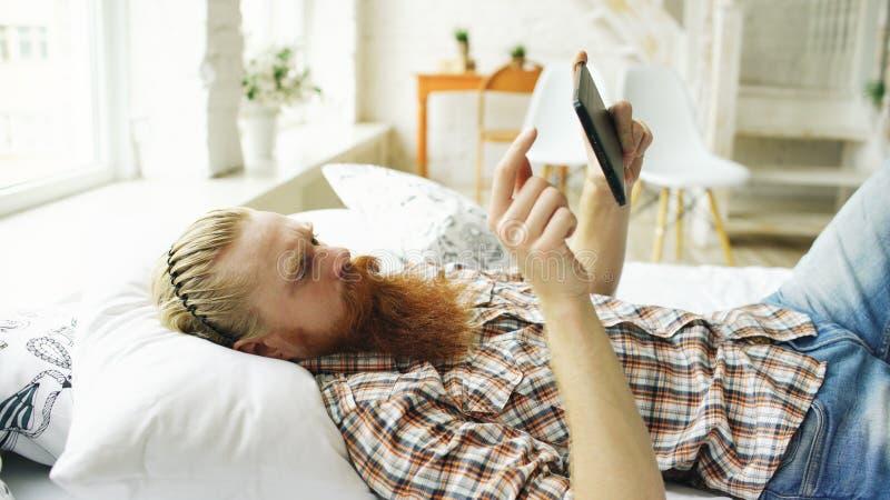使用片剂计算机的年轻有胡子的人在家说谎在床上在卧室 免版税库存照片