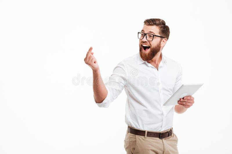 使用片剂计算机的快乐的年轻有胡子的人 免版税库存图片