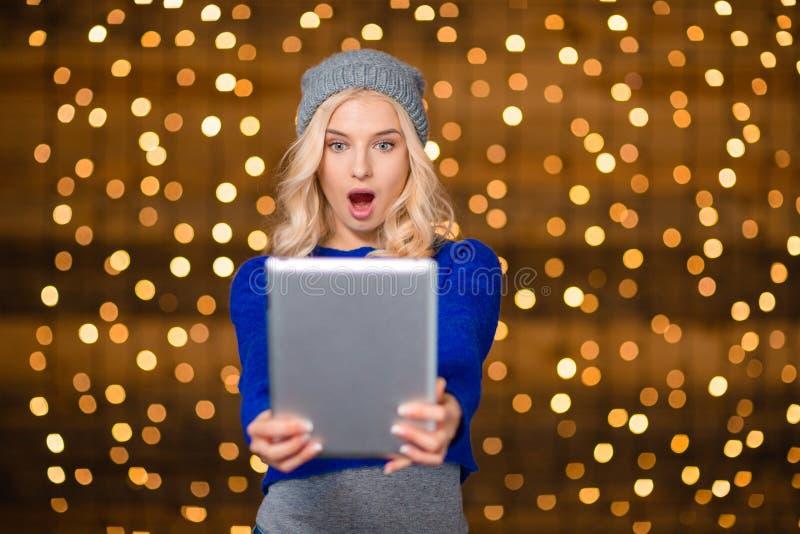 使用片剂计算机的惊奇白肤金发的妇女 免版税库存图片