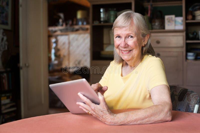 使用片剂计算机的愉快的妇女 免版税库存图片
