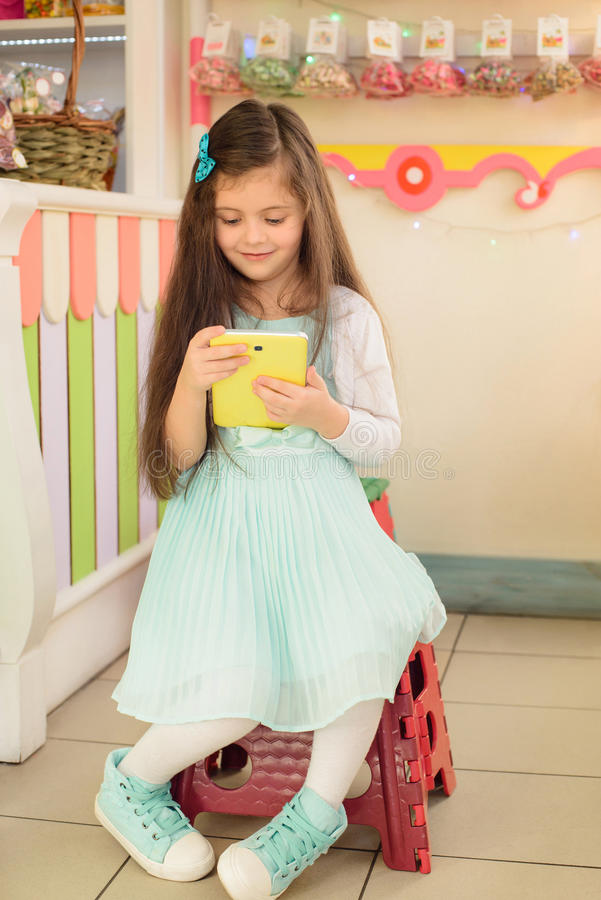 使用片剂计算机的愉快的小女孩在糖果店 免版税库存照片