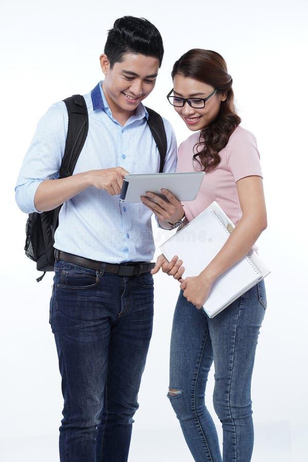 使用片剂计算机的愉快的年轻学生夫妇,隔绝在白色背景 免版税库存照片