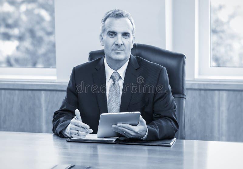 使用片剂计算机的成熟商人 免版税库存照片