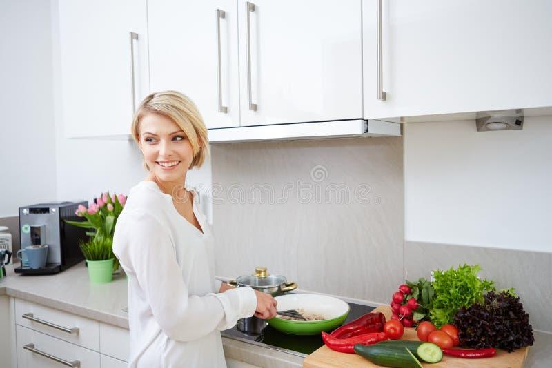 使用片剂计算机的白肤金发的妇女烹调 库存照片