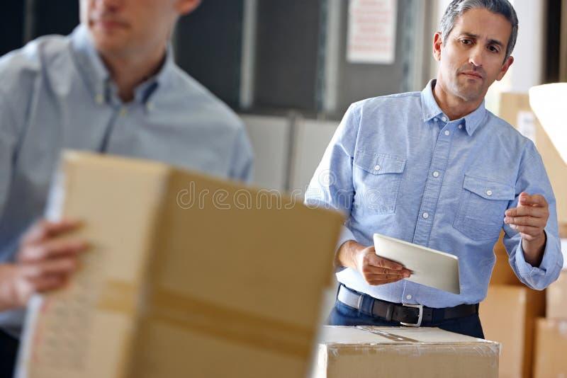 使用片剂计算机的经理在配给物仓库 库存照片