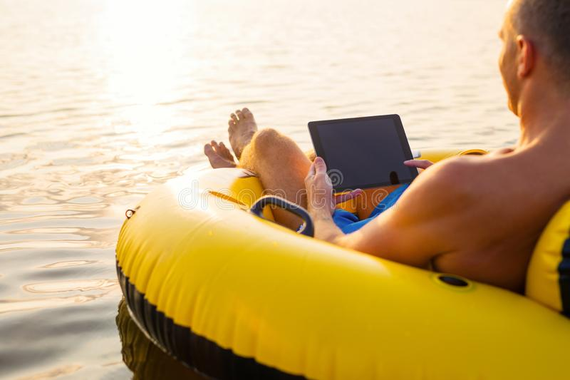 使用片剂计算机的轻松的人在可膨胀的圆环在水中在日落 免版税库存图片