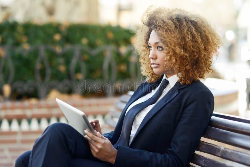 使用片剂计算机的黑人妇女在镇里 免版税库存照片