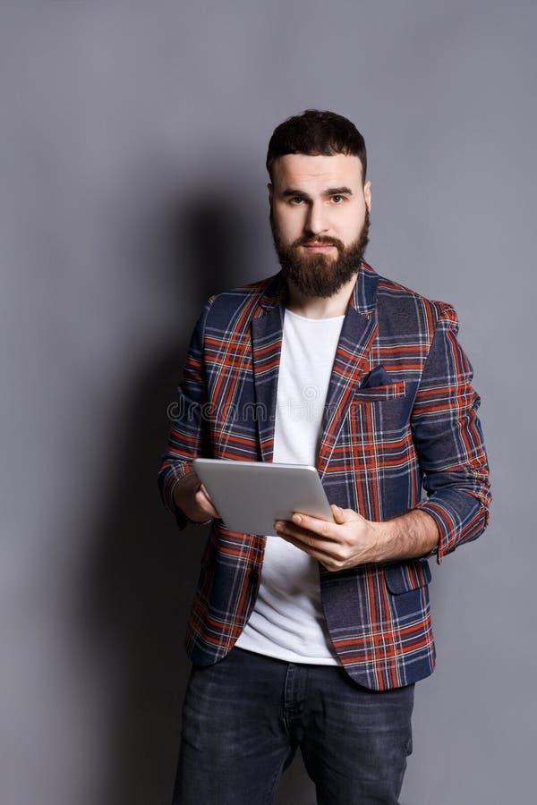 使用片剂计算机的年轻有胡子的人 库存照片