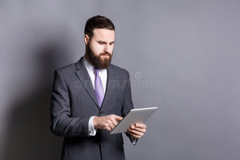 使用片剂计算机的年轻有胡子的商人 免版税库存图片