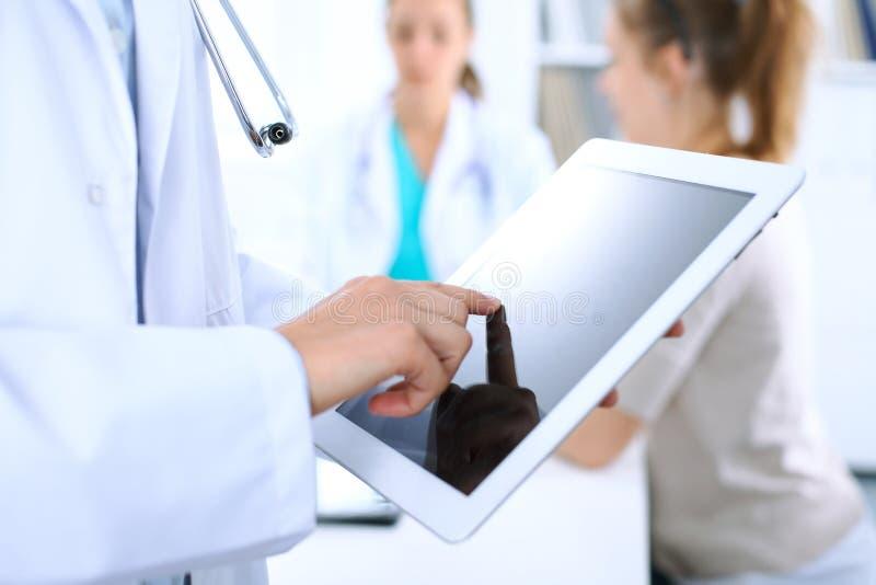 使用片剂计算机,手特写镜头的医生在触摸板屏幕的 免版税图库摄影