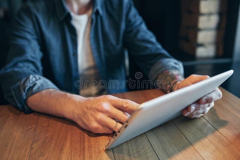使用片剂,连接的wifi的接近的手人 工作从咖啡馆 库存图片