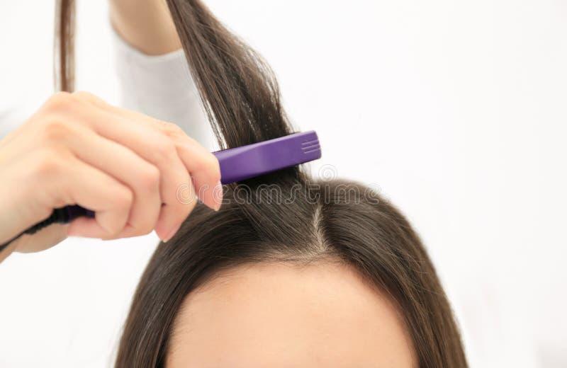 使用现代平的铁的美发师称呼在沙龙的客户的头发 免版税库存照片