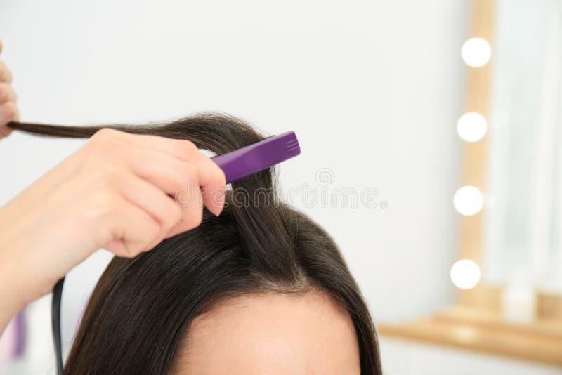 使用现代平的铁的美发师称呼在沙龙,特写镜头的客户的头发 免版税图库摄影