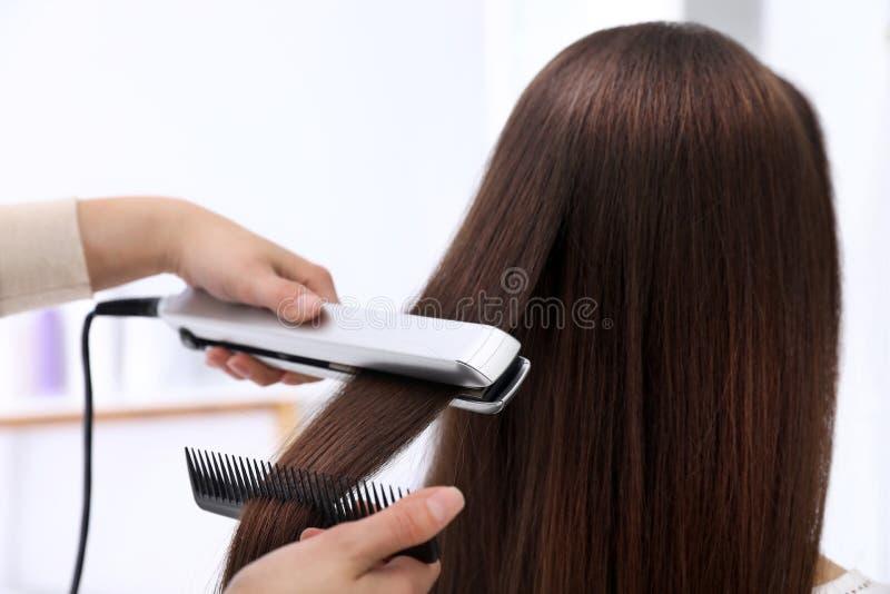 使用现代平的铁的美发师称呼客户的头发 免版税库存图片