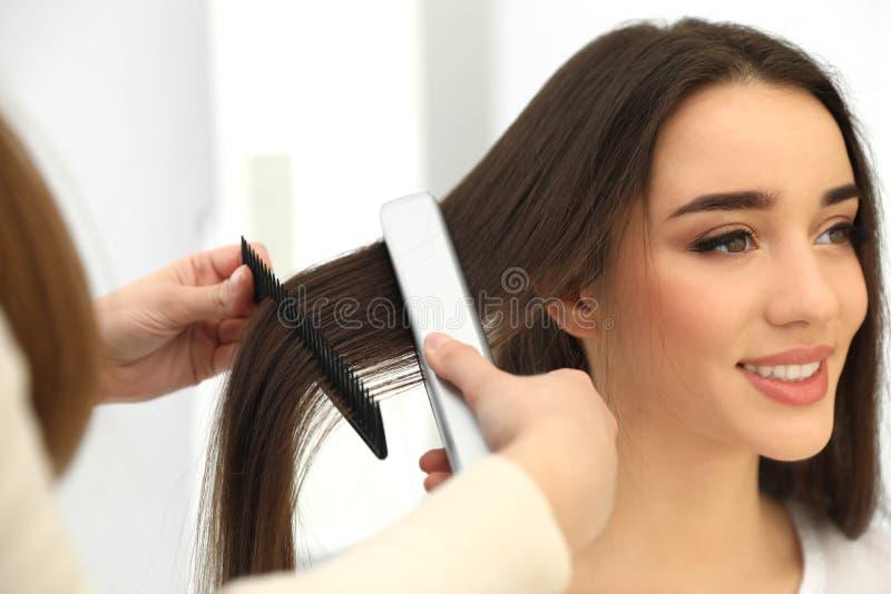 使用现代平的铁的美发师称呼客户的头发 库存图片