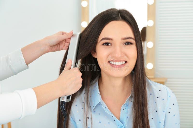 使用现代平的铁的美发师称呼客户的头发 免版税图库摄影