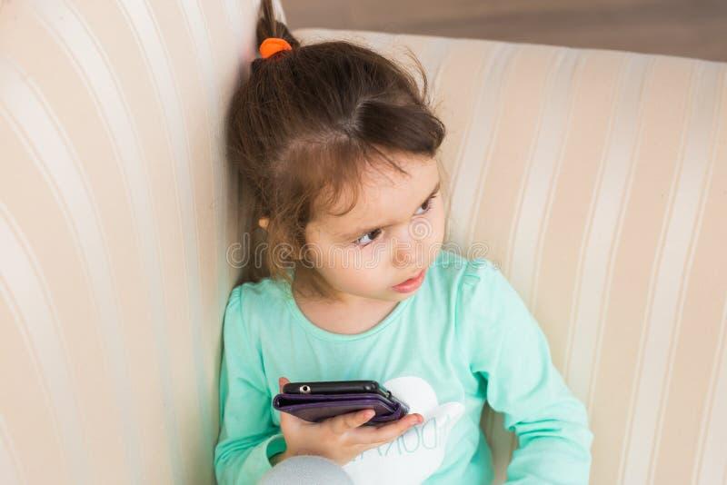 使用现代智能手机的逗人喜爱的小女孩 免版税库存图片