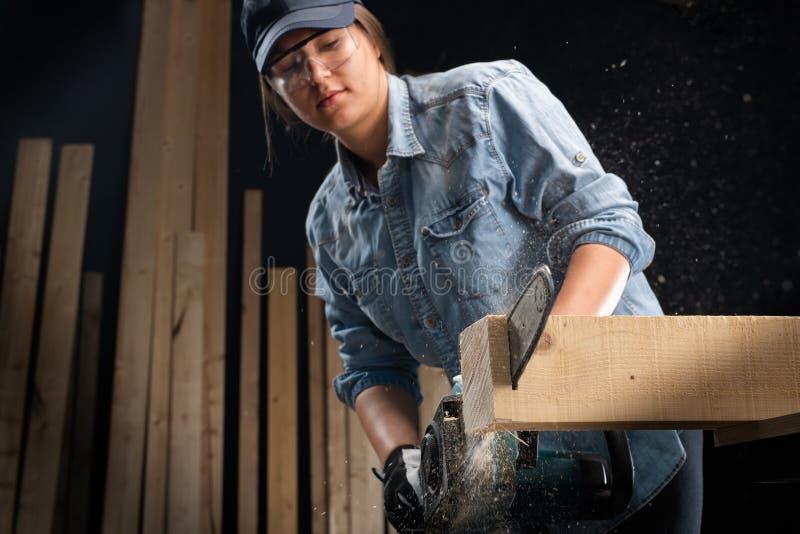 使用现代电锯的年轻女人在车间 库存照片