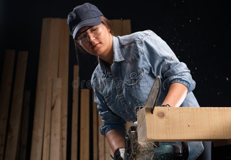 使用现代电锯的年轻女人在车间 免版税库存照片